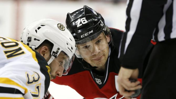 New Jersey Devils left wing Patrik Elias, center, of the Czech Republic, keeps his eye on the puck before facing off against Boston Bruins center Patrice Bergeron (37) during the second period of an NHL hockey game, Friday, Feb. 27, 2015, in Newark, N.J. (AP Photo/Julio Cortez)