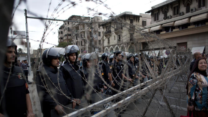 Egyptian riot police stand guard behind barbed wire while protesters chant anti Muslim Brotherhood slogans during a demonstration in front of the presidential palace, in Cairo, Egypt, Tuesday, Dec. 4, 2012. Thousands of Egyptians massed in Cairo Tuesday for a march to the presidential palace to protest the assumption by the nation's Islamist president of nearly unrestricted powers and a draft constitution hurriedly adopted by his allies. (AP Photo/Nasser Nasser)