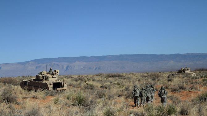 A group of soldiers proceed toward armored vehicles after a training exercise at Ft. Bliss, Texas, Wednesday, Jan. 23, 2013. The army is rolling out a new training platform that allows the integration of live units, simulators and computer generated forces. It is expected to allow cheaper, more frequent training. (AP Photo/Juan Carlos Llorca)