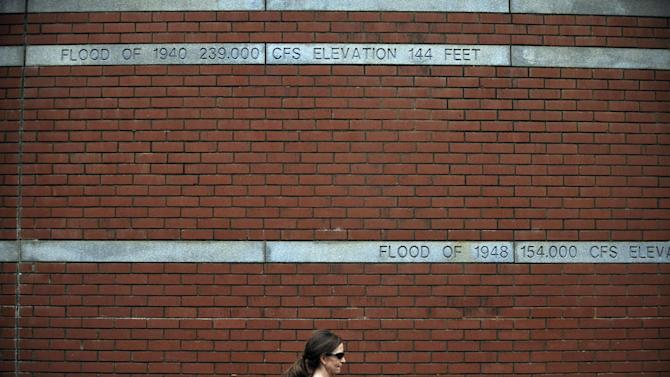 In this Jan. 9, 2013 photo, a woman walks by a brick wall with markers indicating the levels of past floods from the Savannah River in Augusta, Ga. Inspectors with the U.S. Army Corps of Engineers taking the first-ever inventory of flood control systems overseen by the federal government have found hundreds of structures at risk of failing and endangering people and property in 37 states. (AP Photo/Rainier Ehrhardt)