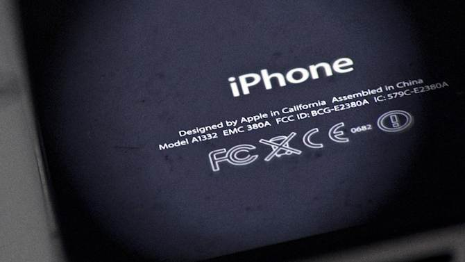 The back of an iPhone 4 and IPad 3 are displayed for a photographer in New York, Thursday, Dec. 6, 2012. Apple CEO Tim Cook said Thursday the company will produce one of its existing lines of Mac computers in the United States next year. Like most consumer electronics companies, Apple forges agreements with contract manufacturers to assemble its products overseas. (AP Photo/Karly Domb Sadof)