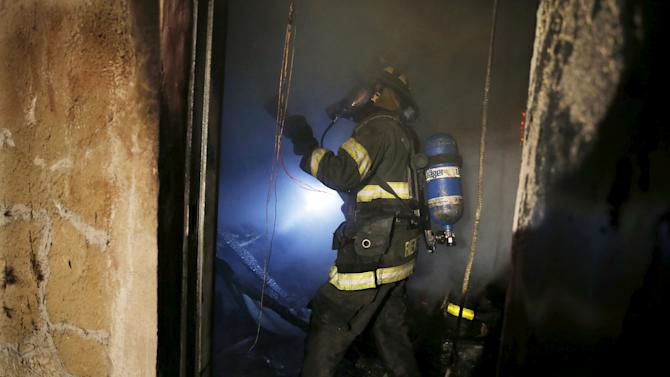 A Baltimore firefighter fights a fire inside a burning building set ablaze by rioters during clashes in Baltimore