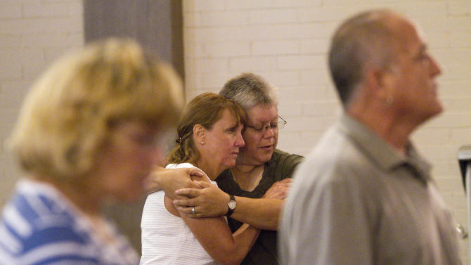 """Judy Goos, left, is embraced by her friend Lisa Stevens at the Grant Avenue United Methodist Church in Aurora, Colo. on Sunday, July 22, 2012, two days after a shooting rampage at a midnight showing of """"The Dark Knight Rises"""" Batman movie. She arrived minutes after the shooting since her daughter Emma Goos, 19, was in theater nine and called her right after she called 911. Her husband is the pastor of the church. (AP Photo/Barry Gutierrez)"""