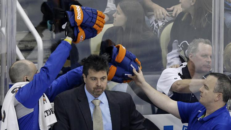 New York Islanders coach Jack Capuano, center, stands behind his bench during the first period of of Game 1 of the Islanders' NHL hockey Stanley Cup first-round playoff series against the Pittsburgh Penguins, Wednesday, May 1, 2013, in Pittsburgh. (AP Photo/Gene J. Puskar)