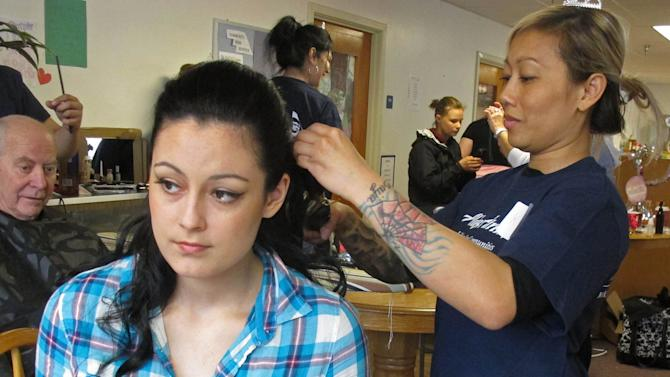 In this photo taken March 30, 2013, in Sitka, Alaska, volunteer hair stylist Khit Sypakanphay of Anchorage, Alaska, right, fixes the hair of Mount Edgecumbe High School student Kaitlyn Love of King Cove, Alaska, before her prom. Mount Edgecumbe is Alaska's only boarding school, and many of the 360 students who attended prom come from more than a hundred Alaska villages. Employees and retirees of Seattle-based Alaska Airlines are in the fifth year of the Prom Princess program, which secures donated dresses and brings in hair stylists and nail artists to get the students ready for their prom. (AP Photo/Mark Thiessen)