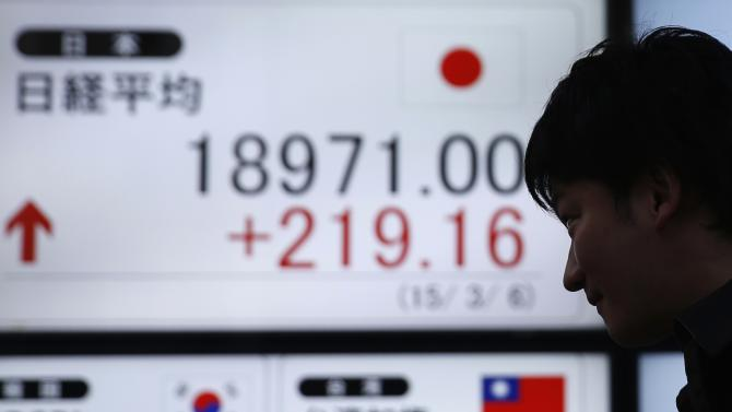 Man walks past an electronic board showing Japan's Nikkei average outside a brokerage in Tokyo