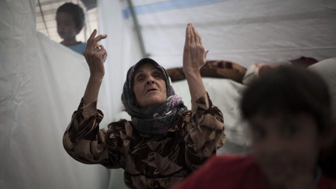 """An elderly Syrian woman, who fled her home with her family due to fighting between government forces and rebels, chants, """"Allah,"""" meaning God in Arabic, inside her tent at a refugee camp near the Turkish border, in Azaz, Syria, Sunday, Oct. 7, 2012. (AP Photo/ Manu Brabo)"""