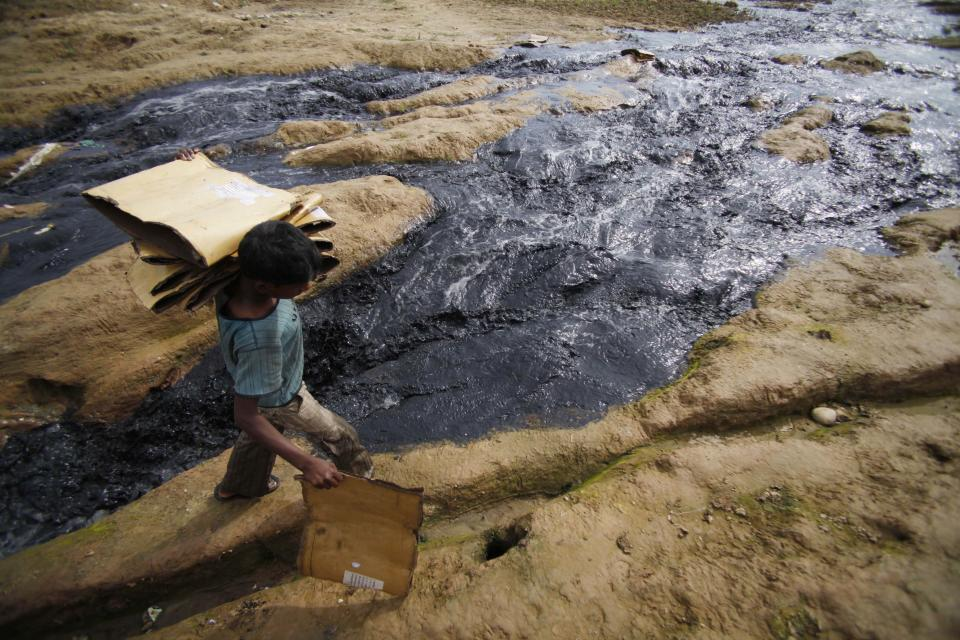 An Indian rag picker walks through contaminated water flowing out of an industrial unit in Jammu, India, Sunday, April 22, 2012. April 22 is observed as Earth Day every year as a tool to raise ecological awareness. (AP Photo/Channi Anand)