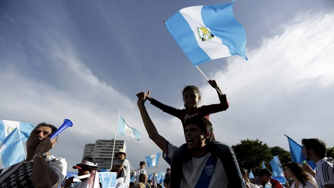 Man carries a girl waving a Guatemalan national flag during a demonstration to demand the resignation of Guatemalan President Otto Perez in downtown Guatemala City