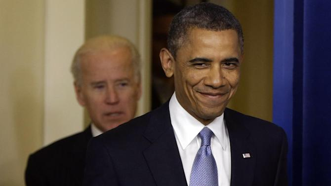 President Barack Obama smiles as he arrives with Vice President Joe Biden to make a statement regarding the passage of the fiscal cliff bill in the Brady Press Briefing Room at the White House in Washington, Tuesday, Jan. 1, 2013. (AP Photo/Charles Dharapak)