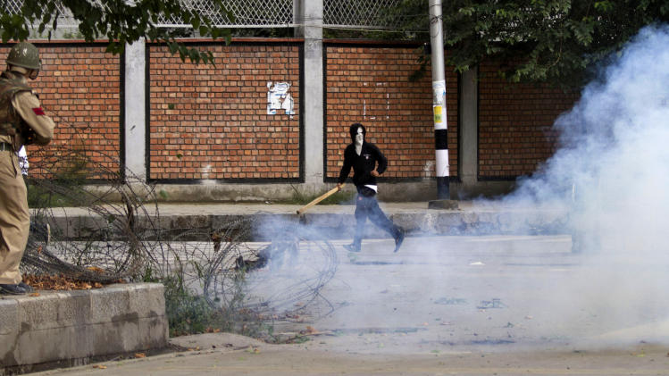 An Indian policeman aims a tear gas gun towards a masked Kashmiri Muslim protester during a protest in Srinagar, India, Tuesday, Sept. 18, 2012, as part of widespread anger across the Muslim world about a film ridiculing Islam's Prophet Muhammad.(AP Photo/ Dar Yasin)