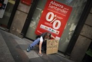 A man with a sign reading ''Help me, I am hungry'' asks for money in front of a bank in Madrid on June 9. Spanish borrowing costs roared to a euro-era record high Tuesday on a market beset by doubts over a vast rescue loan for the country's banks and by fears of a Greek exit from the eurozone