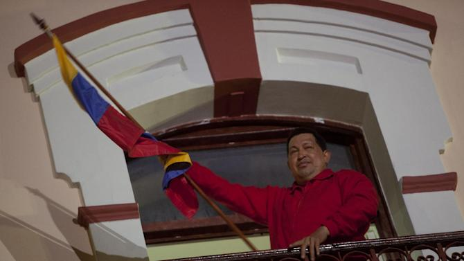 Venezuela's President Hugo Chavez holds a Venezuelan flag as he greets his supporters from the Miraflores presidential palace balcony in Caracas, Venezuela, Sunday, Oct. 7, 2012.  Chavez won re-election and a new endorsement of his socialist project Sunday, surviving his closest race yet after a bitter campaign against opposition candidate Henrique Capriles.(AP Photo/Rodrigo Abd)