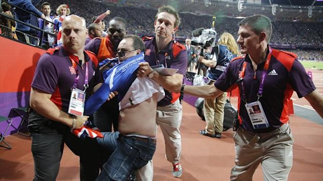 A man is detained by security for throwing a bottle at the starting blocks during the men's 100 metres final at the London 2012 Olympic Games in London (Reuters)