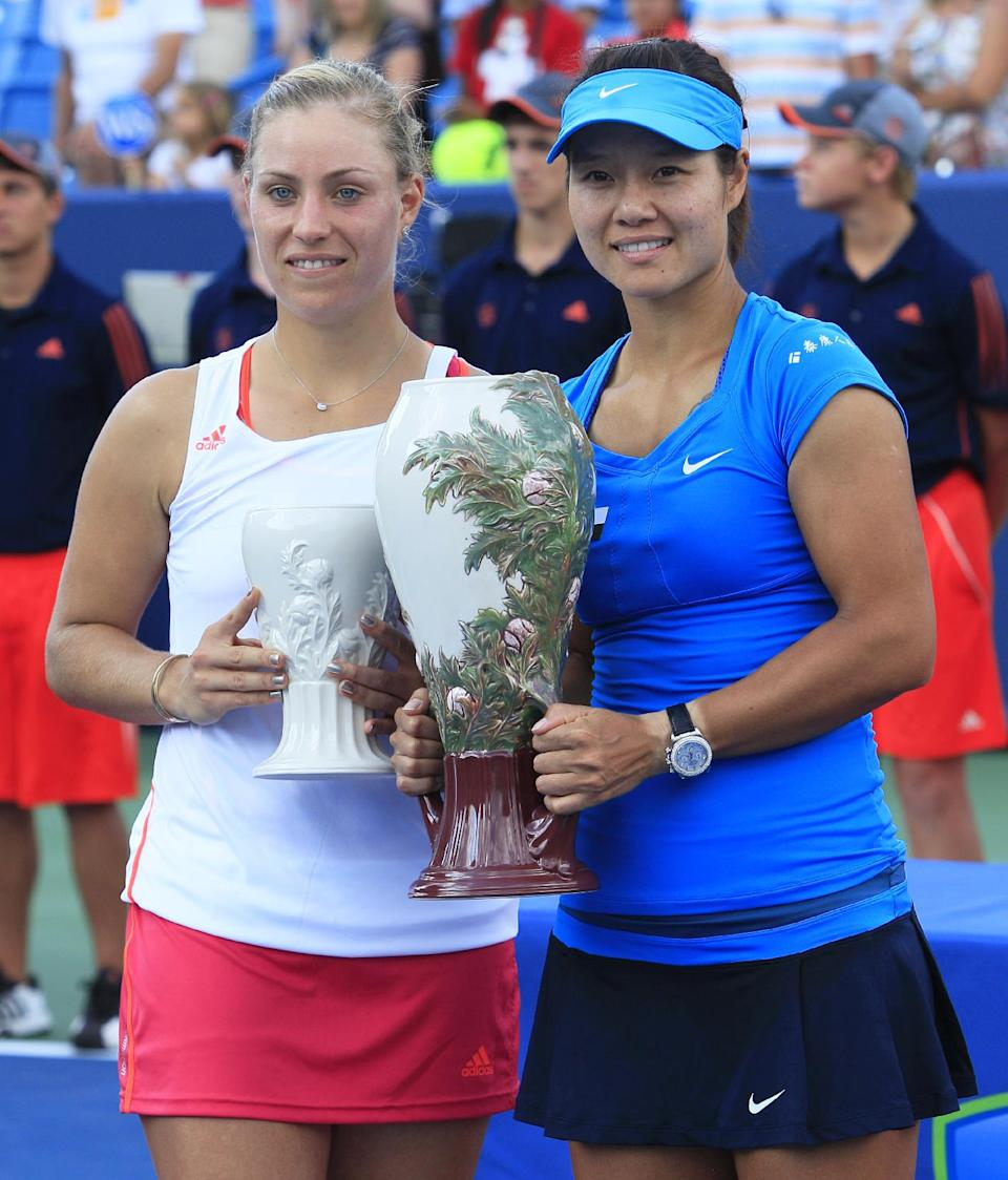 Angelique Kerber, of Germany, left, and Li Na pose with their trophies after the women's final at the Western & Southern Open tennis tournament, Sunday, Aug. 19, 2012, in Mason, Ohio. Na won 1-6, 6-3, 6-1. (AP Photo/Al Behrman)