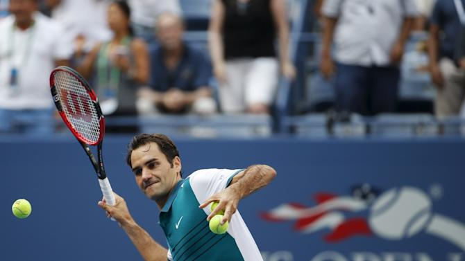 Federer of Switzerland hits a ball into the stands after defeating Mayer of Argentina in their first round match at the U.S. Open Championships tennis tournament in New York