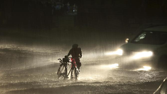 An Indian man walks with his cycle through a water-logged street as it rains in Jammu, India, Monday, June 29, 2015. Heavy rains lashed the city bringing much needed relief from the scorching heat wave. (AP Photo/Channi Anand)