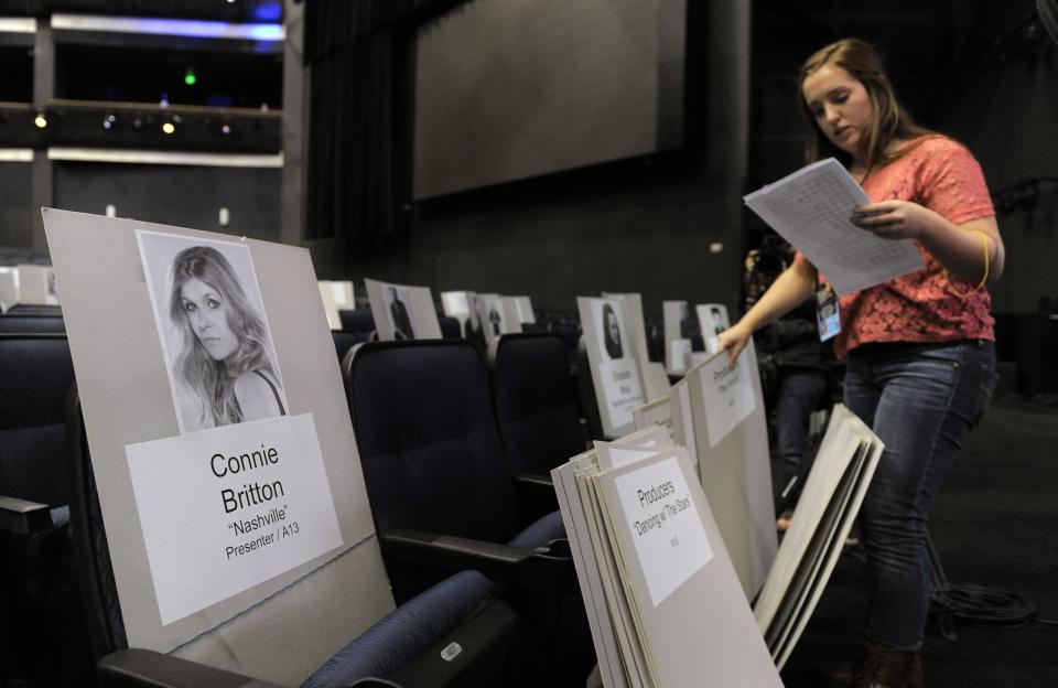 Lindsay Saunders, right, organizes placards deciding where attendees will sit for Sunday's 65th Emmy Awards, during Emmy Awards Press Preview Day, on Wednesday, Sept. 18, 2013, at Nokia Theatre in Los Angeles. (Photo by Chris Pizzello/Invision/AP)