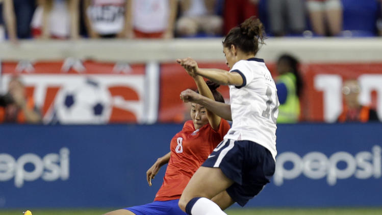 South Korea's Cho Sohyun, left, tries to slide tackle United States' Carli Lloyd during the first half of an international friendly soccer match at Red Bull Arena, Thursday, June 20, 2013, in Harrison, N.J. (AP Photo/Julio Cortez)
