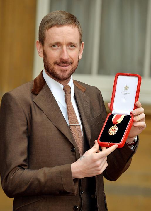 Britain's  Bradley Wiggins proudly holds his  award of a Knighthood, after it was presented to him by the Queen at the Investiture ceremony at Buckingham Palace in central London Tuesday Dec. 10,