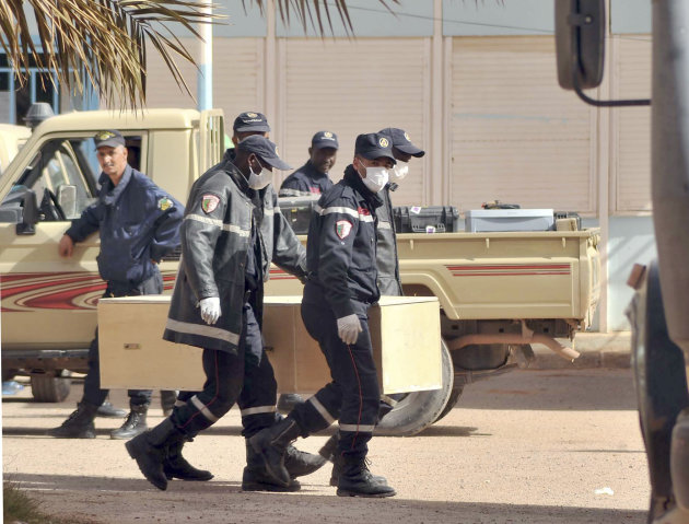 Algerian firemen carry a coffin containing a person killed during the gas facility hostage situation at the morgue in Ain Amenas, Algeria, Monday, Jan. 21, 2013. At least 81 people have been reported
