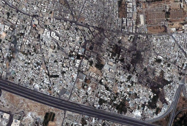 This a satellite image provided by DigitalGlobe of the Qabun neighborhood in Damascus, Syria was acquired July 18, 2012. The satellite imagery shows a tank on 6th Rishreen road in the lower left portion of the image as well as a smoking building on the feeder portion of the exchange. Vehicle tracks and possible rubble are visible on the road just above the smoking building. Five additional tanks or armored vehicles are located elsewhere in Qabun, encircling the neighborhood. (AP Photo/DigitalGlobe)