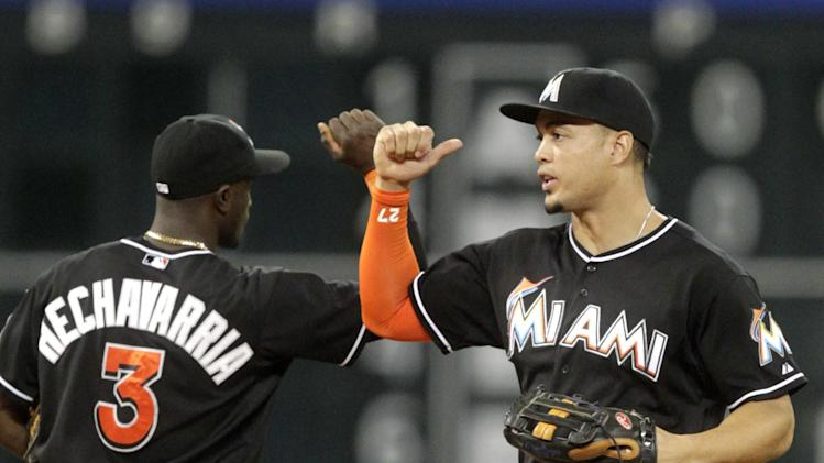 Miami Marlins' Adeiny Hechavarria (3) and Giancario Stanton celebrate after the Marlins defeated the Houston Astros 2-0 in a baseball game, Friday, July 25, 2014, in Houston. (AP Photo/Patric Schneider)
