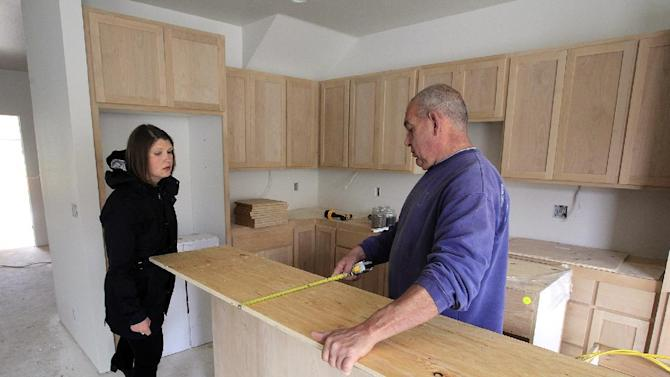 In this May 15, 2015 photo, Mandi Butler, left, of Future B Homes, talks with finish carpenter Darrell Fosback at a home under construction in Eugene, Ore. More Americans bought new homes in April — fresh evidence that the improved job market is powering the real estate sector. (Paul Carter/The Register-Guard via AP)