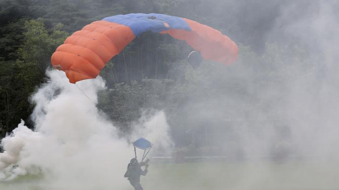A paratrooper lands amidst smoke during the 79th anniversary celebration of the Armed Forces of the Philippines in Quezon city