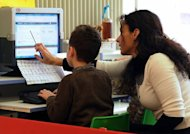 "File picture shows a teacher helping a child use Twitter at a school in France. Twitter said a ""cascading bug"" caused outages affecting millions of users of the wildly popular site, and dismissed claims of a hacker attack"