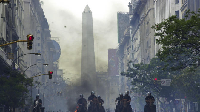 """FILE - In this Dec. 20, 2001 file photo, mounted police charge anti-government demonstrators in Buenos Aires, Argentina. Argentina had just defaulted on more than $100 billion in foreign debt, banks were shuttered, the economy was in ruins and streets were filled with pot-banging protesters whose chants of """"throw them all out"""" would send five presidents packing.  Argentina's government is now celebrating their upcoming Aug. 3, 2012 payoff of ten-year bonds given to people whose savings were confiscated a decade ago, suggesting it is a lesson for European countries now mired in foreign debt. (AP Photo/Walter Astrada, File)"""