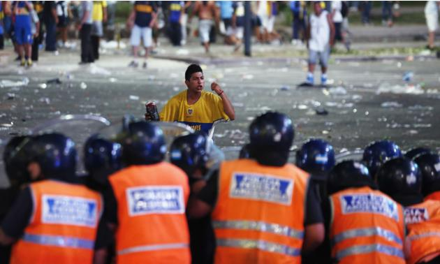 A fan of Argentine soccer team Boca Juniors confronts police during riots after celebrations of Boca Juniors Fan Day in downtown Buenos Aires