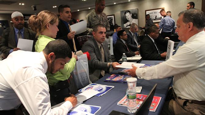 In this  Friday Sept. 28, 2012, photo, Veteran Luis Gomez, 40, from Dover, N.J., seated center, hands his resume to a representative from White Rose Foods, right, during a job fair at Yankee Stadium in the Bronx borough of New York. A private survey relased Wednesday, Oct. 3, 2012, shows that U.S. businesses hired fewer workers in September than August, a sign that slow growth may be holding back hiring.  Payroll processor ADP said Wednesday that companies added 162,000 jobs last month. That's below August's total of 189,000, which was revised lower. (AP Photo/Tina Fineberg)