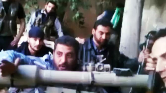 In this image taken from video obtained from the Ugarit News, which has been authenticated based on its contents and other AP reporting, Colonel Abu al-Furat, commander of the battle of the trenches revolutionaries, second left, speaks in Aleppo, Syria, on Monday, Nov. 26, 2012. (AP Photo/Ugarit News via AP video)
