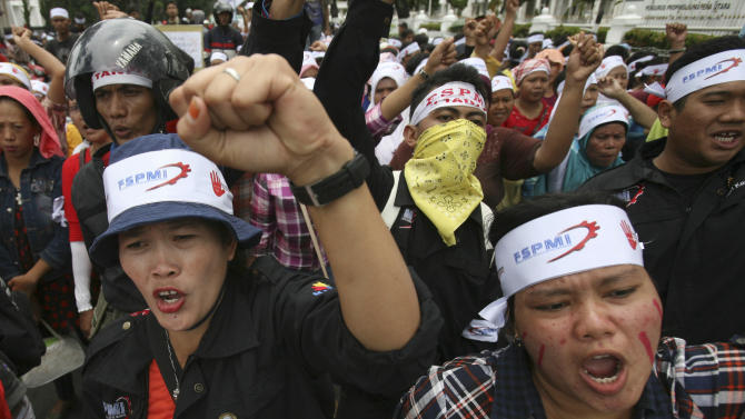 Factory workers shout slogans during a protest in medan, North Sumatra, Indonesia, Wednesday, Oct. 3, 2012. Indonesian unions said more than 2 million factory workers have gone on a one-day strike across the country to call for higher wages and protest the hiring of contract workers. (AP Photo/Binsar Bakkara)