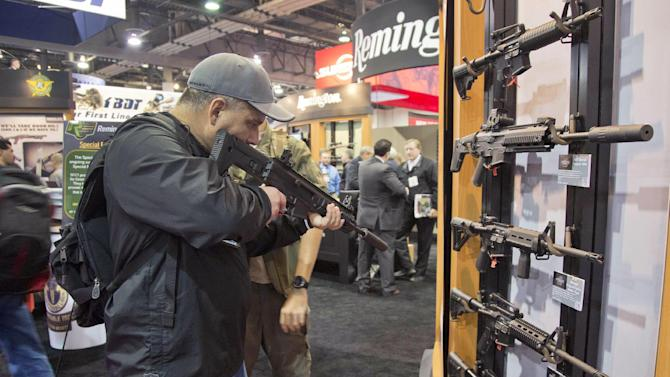 Stuart Konicar of Scottsdale, Ariz., looks down the sight of a Remington Adaptive Combat Rifle on display at the Remington Defense exhibit during the 35th annual SHOT Show, Tuesday, Jan. 15, 2013, in Las Vegas. The rifle, not available for commercial sale, was on display for industry professionals at the trade show which is put on by the National Shooting Sports Foundation. (AP Photo/Julie Jacobson)