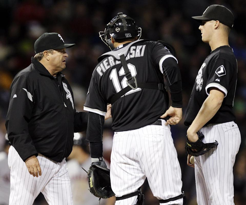 Chicago White Sox pitching coach Don Cooper, left, talks with catcher A.J. Pierzynski, center, and relief pitcher Nate Jones during the sixth inning of a baseball game against the Cleveland Indians in Chicago, Wednesday, Sept. 26, 2012. (AP Photo/Nam Y. Huh)