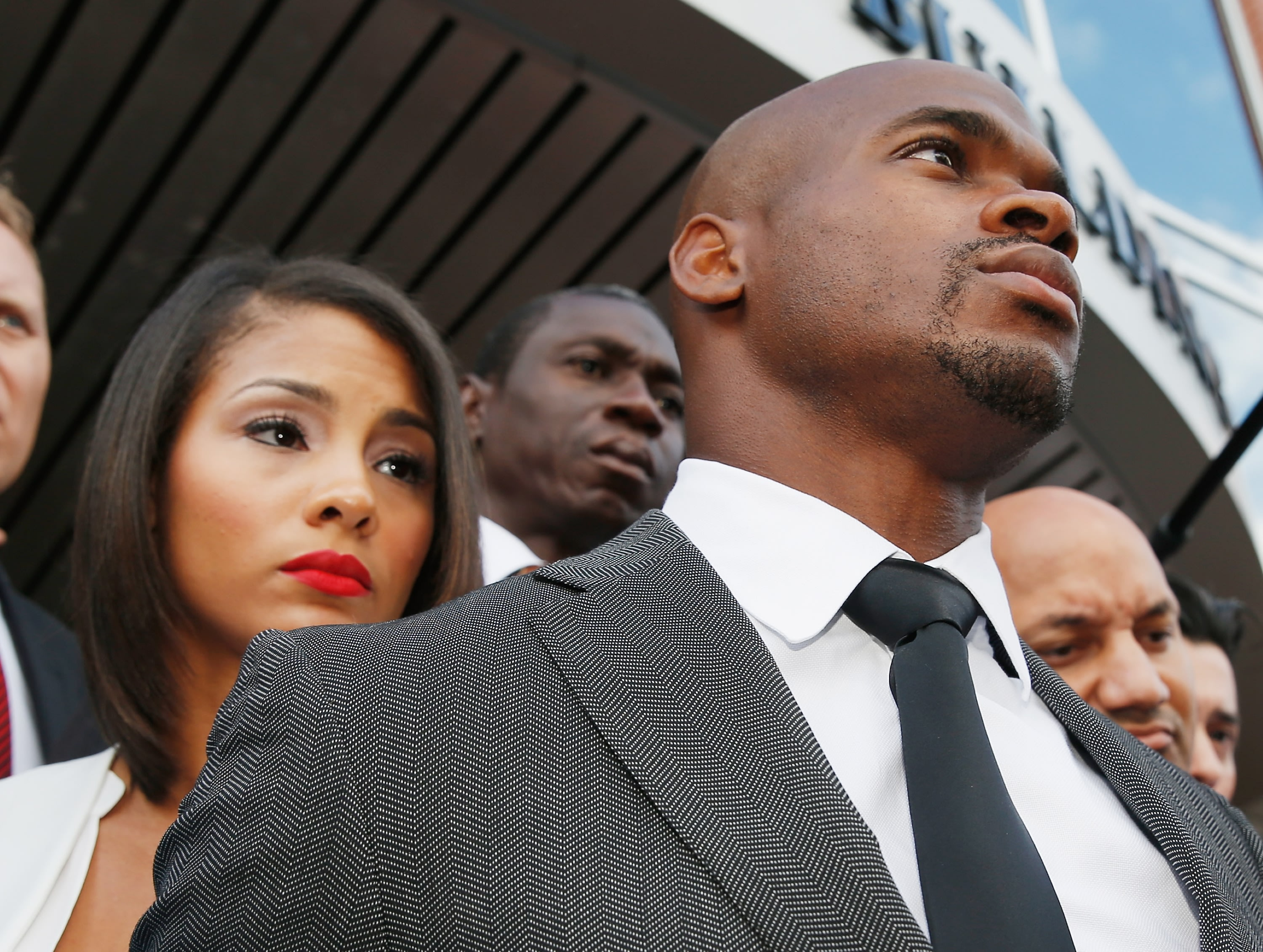 CONROE, TX - OCTOBER 08:  NFL player Adrian Peterson of the Minnesota Vikings waits with his wife Ashley Brown after making a court appearance at the Montgomery County municipal building on October 8, 2014 in Conroe, Texas. Peterson did not enter a plea, and after about an hour in the courtroom the hearing was reset. A tentative trial date was set for Dec. 1. Petersen is facing charges of reckless or negligent injury to a child.  (Photo by Scott Halleran/Getty Images)