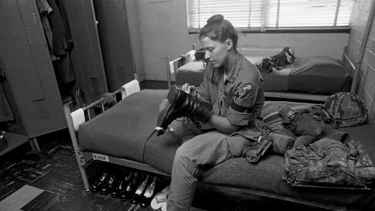 FILE - In this Sept. 21, 1977, file photo, recruit Angelia Wingle, of Lyons Ga., shines her combat boot as she sits on a bunk in the barracks at Fort Jackson, S.C. (AP Photo/Lou Krasky)