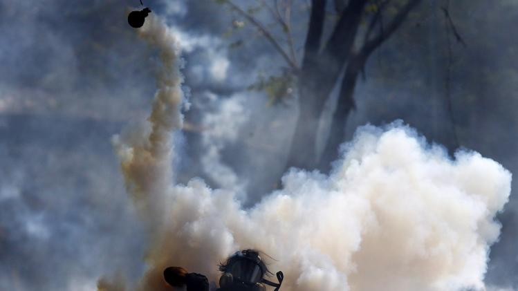 An anti-government protester throws a gas canister back to the police during clashes in Caracas