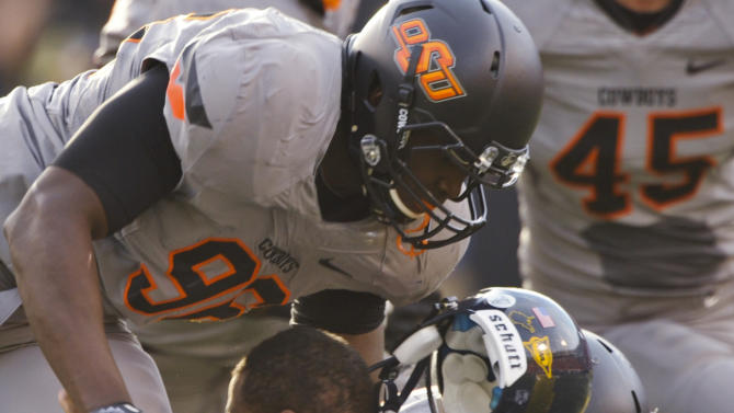 Oklahoma State's Ryan Robinson, left, and Christian Littlehead tackle West Virginia quarterback Geno Smith during the first half of an NCAA college football game in Stillwater, Okla., Saturday, Nov. 10, 2012. Oklahoma State won 55-34. (AP Photo/Brody Schmidt)