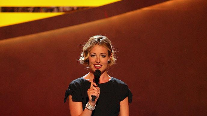 "Cat Deeley wore a fitted black dress by John Galliano for Dior for the Top 12 performance show of ""So You Think You Can Dance"" Season 5. The stylish host accessorized the sophisticated look with vintage bracelets, a vintage broach in her hair, and bejeweled T-strap sandals by Sergio Rossi."