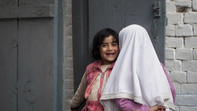 In this Wednesday, Nov. 14, 2012 photo, Shazia Ramazan's little sister Nazia, 5, left, plays with a friend at their home in Mingora, Swat Valley, Pakistan. Shazia Ramazan, 13, was  wounded by the same Taliban gunman, who shot Malala Yousufzai and 16-year-old Kainat Riaz Oct 8, 2012 on their way coming back from school. Malala was shot for her outspoken insistence on girls education. Shazia and Kainat are to return to school this week for the first time since the shooting more than one month ago. ( AP Photo/Anja Niedringhaus)