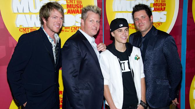 Jay DeMarcus, left, Gary LeVox, Justin Bieber, and Joe Don Rooney arrive at the 2011 CMT Music Awards in Nashville, Tenn. on Wednesday, June 8, 2011. (AP Photo/Charles Sykes)