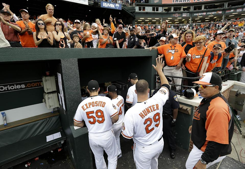Baltimore Orioles starting pitcher Tommy Hunter (29) acknowledges fans as he follows teammates into the clubhouse after a baseball game against the Boston Red Sox in Baltimore, Sunday, Sept. 30, 2012. (AP Photo/Patrick Semansky)