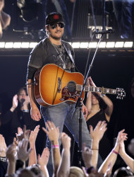 "FILE - In this Nov. 9, 2011 file photo, Eric Church performs ""Drink In My Hand"" during the 45th Annual CMA Awards in Nashville, Tenn. Church's fans smashed chairs and threw bottles and cans after his planned concert in Buffalo, N.Y., was canceled due to bad weather. The Buffalo News reports said organizers of the WYRK Taste of Country concert decided to halt the multi-act show at around 11 p.m., Friday, June 1, 2012, after strong winds threatened the stage at Buffalo's Coca Cola Field. Church had originally been scheduled to go on at about 9:45 p.m. The singer issued a statement saying he was ""bummed"" about the cancellation, but planned to return to Buffalo at a later date. (AP Photo/Mark Humphrey, File)"