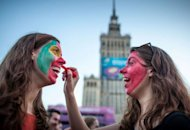 Portugal fans paint each other's faces in the Warsaw fan zone as they prepare to watch the Euro 2012 quarter-final match against the Czech Republic