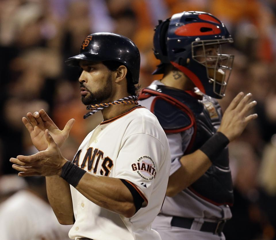 San Francisco Giants' Angel Pagan reacts in front of St. Louis Cardinals catcher Yadier Molina after scoring on a hit by Marco Scutaro during the fourth inning of Game 2 of baseball's National League championship series Monday, Oct. 15, 2012, in San Francisco. (AP Photo/David J. Phillip)