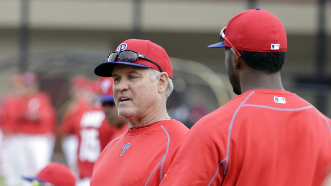 Philadelphia Phillies manager Ryne Sandberg, left, talks with left fielder Domonic Brown, right, during a spring training baseball workout, Friday, Feb. 27, 2015, in Clearwater, Fla. (AP Photo/Lynne Sladky)