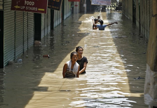 Girls wade through a flooded alley at a shopping arcade after heavy monsoon rains caused the rise in waters of Yamuna river in New Delhi